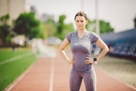Photo for Portrait of a beautiful young caucasian woman with long hair in the tail and big breasts posing in gray sportswear standing training on a running stadium, a red rubber track in summer on a sunny day. - Royalty Free Image