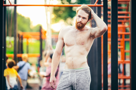 Photo for Subject sport street workout Handsome young caucasian man with a bare-chested muscular with long red hair and beard posing outdoor sports ground, gym outdoors. Sexy guy touches his hair - Royalty Free Image