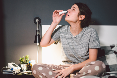 Foto de The theme is seasonal cold, runny nose flu virus infection. Young caucasian woman at home bedroom bed uses spray drops of medicine in her nose for snot. Allergic renitis and sinusitis. - Imagen libre de derechos