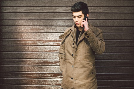 Foto de Portrait of a model young mulatto male Turkish Mediterranean race brunet in coat uses hand phone technology businessman on the street in sunny weather against the background of a wooden wall. - Imagen libre de derechos