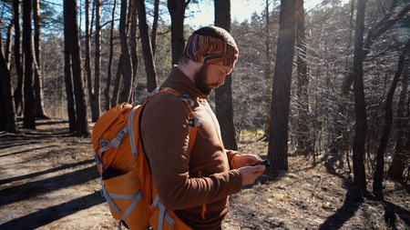 Foto de theme tourism and technology. Young caucasian man with beard and backpack. Hiking tourist in pine forest uses technology, hand holding mobile phone to touch the screen. Gps application orientation. - Imagen libre de derechos