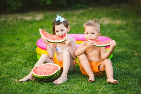 Photo for Funny little kids brother and sister eating watermelon on green grass near inflatable pool in yard at home. - Royalty Free Image