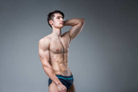 Photo for Young male athlete bodybuilder posing. Handsome athletic male power guy. Fitness muscular person. Young athlete showing muscles in the studio. six packs muscles posing shirtless on gray background. - Royalty Free Image