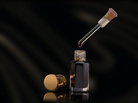 Foto de Incense of Traditional Arabian Fragrance oil in a glass jar and dropper drop on black background - Imagen libre de derechos