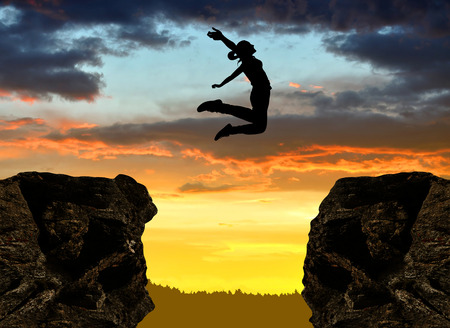 Photo pour Silhouette the girl jumping over the gap at sunset - image libre de droit