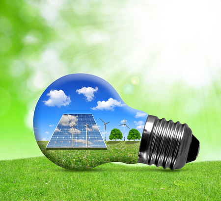 Foto de Solar panels and wind turbines in light bulb. Green energy concept. - Imagen libre de derechos