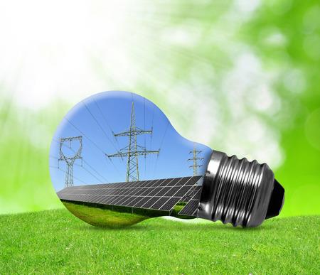 Foto de Solar panels and high voltage pylons in light bulb. Green energy concept. - Imagen libre de derechos