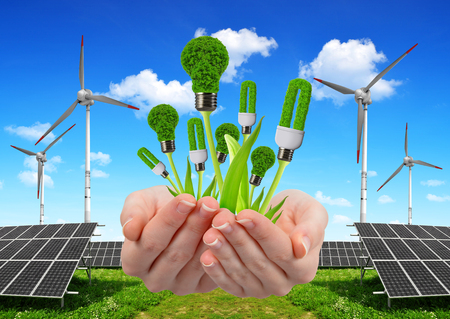 Photo pour Hand holding eco lightbulbs. In the background solar energy panels and wind turbine. Clean energy concept. - image libre de droit