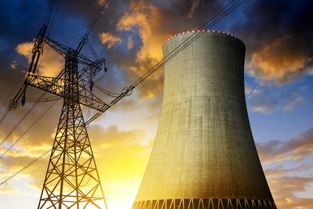 Foto de Nuclear power plant with high voltage towers against the sunset - Imagen libre de derechos