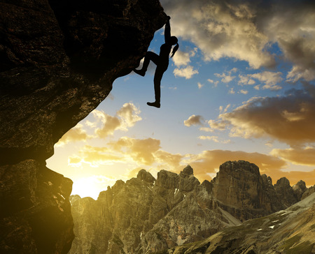 Foto de Silhoutte of girl climbing on rock at sunset in Dolomite Alps , Italy - Imagen libre de derechos