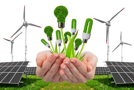 Foto de Hand holding eco lightbulbs. In the background solar energy panels and wind turbine. Clean energy concept. - Imagen libre de derechos