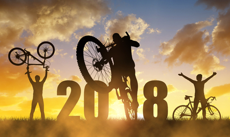 Foto de Cyclist with bicycle at sunset.Forward to the New Year 2018. - Imagen libre de derechos