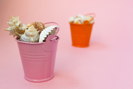 Photo for Two buckets filled with seashells on a pink background. Orange and pink bucket. There is a place for text. Maritime concept. - Royalty Free Image