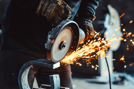Foto de Craftsman sawing metal sparkles all around workshop. Working at noon. - Imagen libre de derechos