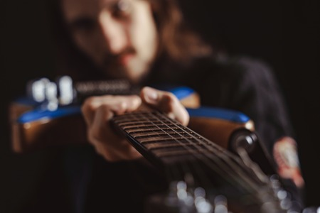 Photo for the guy holds the guitar focus on the fretboard - Royalty Free Image