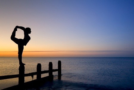 Silhouette of young woman doing exercises on empty beach at sunset