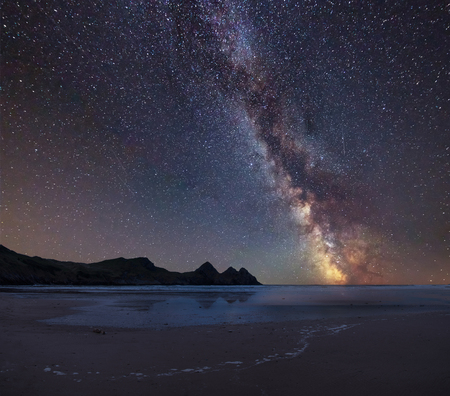 Photo for Stunning vibrant Milky Way composite image over landscape of yellow sandy beach Three Cliffs bay - Royalty Free Image