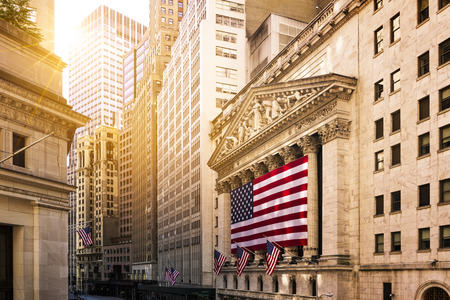 Foto de Famous Wall street and the building in New York, New York Stock Exchange with patriot flag - Imagen libre de derechos