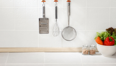 Kitchen cooking utensils on hook against tile wall