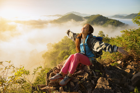 Foto de The adventurer stands at the top of the mountain with foggy morning sky with the shadow of a distant mountain,freedom lifestyle concept traveller with backpacks relaxing. - Imagen libre de derechos