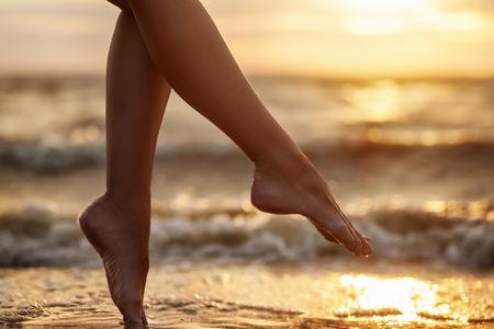 Foto de natural summer background. woman legs on beach - Imagen libre de derechos