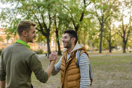 Photo for Two handsome youngsters shaking hands after seeing each other after long time - Royalty Free Image