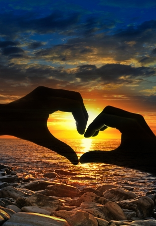 Foto de touching hands in a heart-shaped and sunset - Imagen libre de derechos