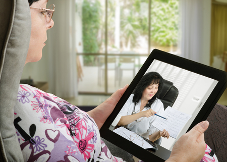 Foto de Mature adult woman consults a telemedicine doctor with tablet computer sitting in soft chair. In touchscreen, female doctor in white uniform reviewing blood pressure report. With telehealth application patient can reach relevant specialist remotely. Horizontal side shot on indoors blurred background - Imagen libre de derechos