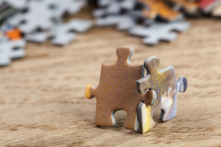 Photo for Two jigsaw puzzle pieces on a table joint together - Royalty Free Image