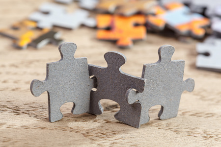 Photo for Three jigsaw puzzle pieces on a table joint together - Royalty Free Image