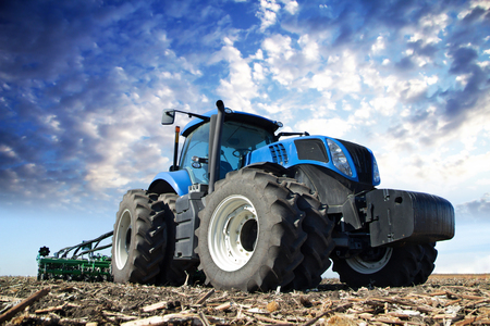 Photo for The tractor wheels on the huge field, a farmer riding a tractor, a tractor working in a field agricultural machinery in the work, tractor in the background cloudy sky - Royalty Free Image