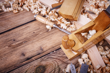 Photo pour Wooden planer, table from old wood, natural building materials, woodwork and antique hand tools, carrying out carpentry, tool kit for joinery, wood sawdust, old wood texture - image libre de droit
