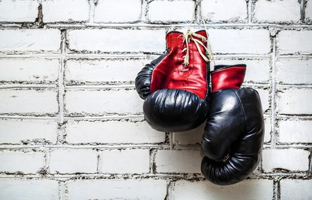 Foto de Pair of old red and black boxing gloves hanging on white brick wall. - Imagen libre de derechos
