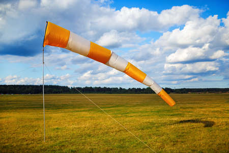 Photo for Windsock at small airfield. Blue sky with clouds and field of grass. - Royalty Free Image