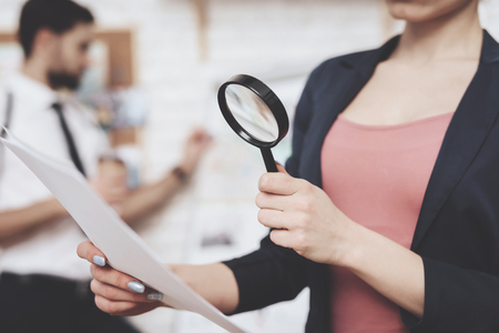 Photo for Private detective agency. Woman in jacket is posing with paper and magnifying glass, man is looking at clues map. - Royalty Free Image