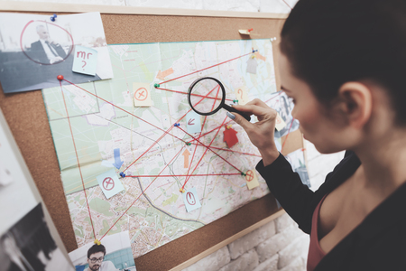 Foto de Private detective agency. Woman in jacket is looking at clue map with magnifying glass in office. - Imagen libre de derechos