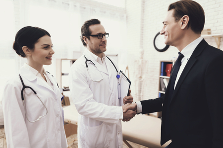 Foto de Happy businessman shaking hands with doctor who cured ailment. Acknowledgments. Medical examination. Treatment of disease. - Imagen libre de derechos