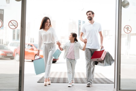 Photo for Family, father, mother and daughter with shopping bags are entering shopping mall. - Royalty Free Image