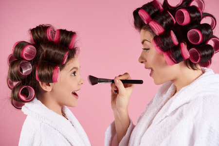 Photo pour Beautiful mother and daughter teenager in curlers doing makeup. Isolated on pink background. Studio portrait. - image libre de droit