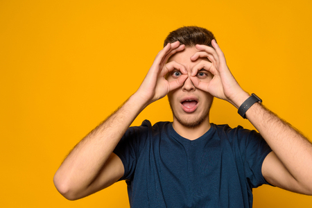 Photo for Young handsome guy shows gesture binocle isolated on yellow background. Studio portrait. - Royalty Free Image