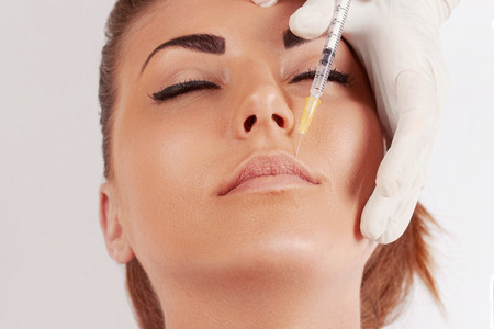 Photo pour Portrait of Beautiful woman gets injection of botox in her lips. Closeup hand in glove with syringe making injection. Female in beauty salon. plastic surgery clinic.Hyaluronic Collagen Injection.Facelift - image libre de droit