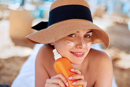 Foto de Facial Care. Young  Female Holding Bottle Sun Cream and  Applying on Face Smiling. Beauty Face.  Portrait Of Young Woman in hat Smear  Moisturizing Lotion on Skin. SkinCare - Imagen libre de derechos