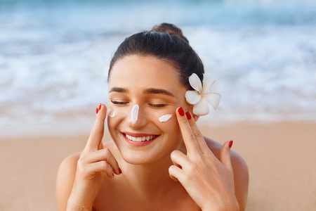 Foto de Beautiful woman applying cream sunscreen on a tanned face. Sunscreen. Skin and body care. The girl uses a sunscreen for her skin. Portrait of a female holding suntan lotion and moisturizing sunscreen. - Imagen libre de derechos