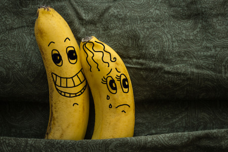 Foto de Two yellow bananas, husband and wife, a metaphor. A man burns with desire, a woman does not want sex. Family relations, incompatibility in bed. The picture is made by the author. - Imagen libre de derechos