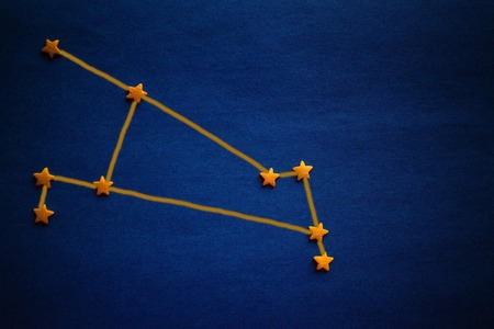 Foto de Brightly yellow stars on a blue background, a schematic arrangement of the constellation Aries. Top view, copy space. The picture is made by the author. - Imagen libre de derechos