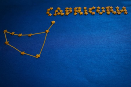 Foto de The constellation Capricorn and the inscription composed of small stars. Horoscope, astrological prediction. Blue background, side lighting. Figure made by the author. - Imagen libre de derechos