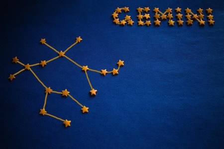 Foto de Yellow stars lined constellation and the inscription Gemini. Astrology, zodiac signs. Vignetting, drawing made by the author. - Imagen libre de derechos