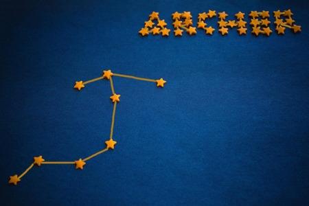 Foto de Astrology, date of birth, zodiac sign. Constellation Archer, element of fire. Blue background, yellow decorative stars. Figure made by the author. - Imagen libre de derechos