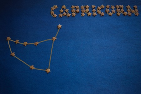 Foto de Constellation Capricorn on a blue background. The inscription is made up of small decorative stars. Astrological prediction. Copy space. Figure made by the author. - Imagen libre de derechos