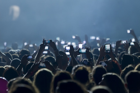 Foto per People taking photographs with touch smart phone during a music entertainment public concert  - Immagine Royalty Free